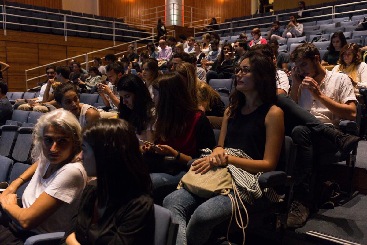 público sentado dentro do pequeno auditório