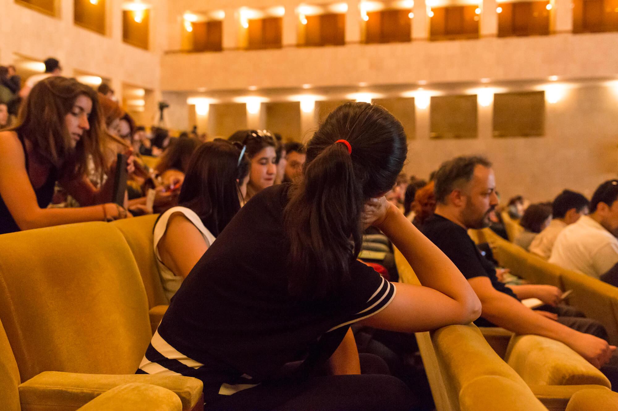 público sentado dentro do grande auditório