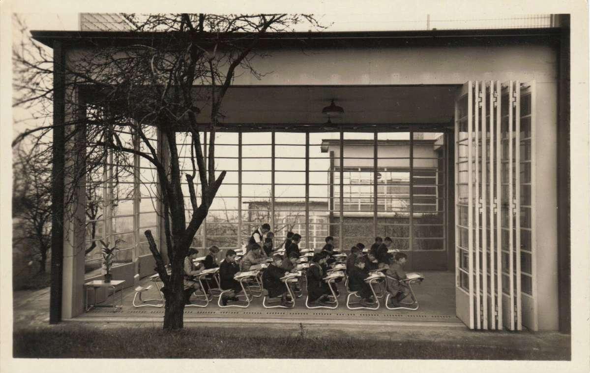foto a preto e branco de uma sala de aulas de crianças pequenas toda em vidro em que a fachda abre para o espaço exterior