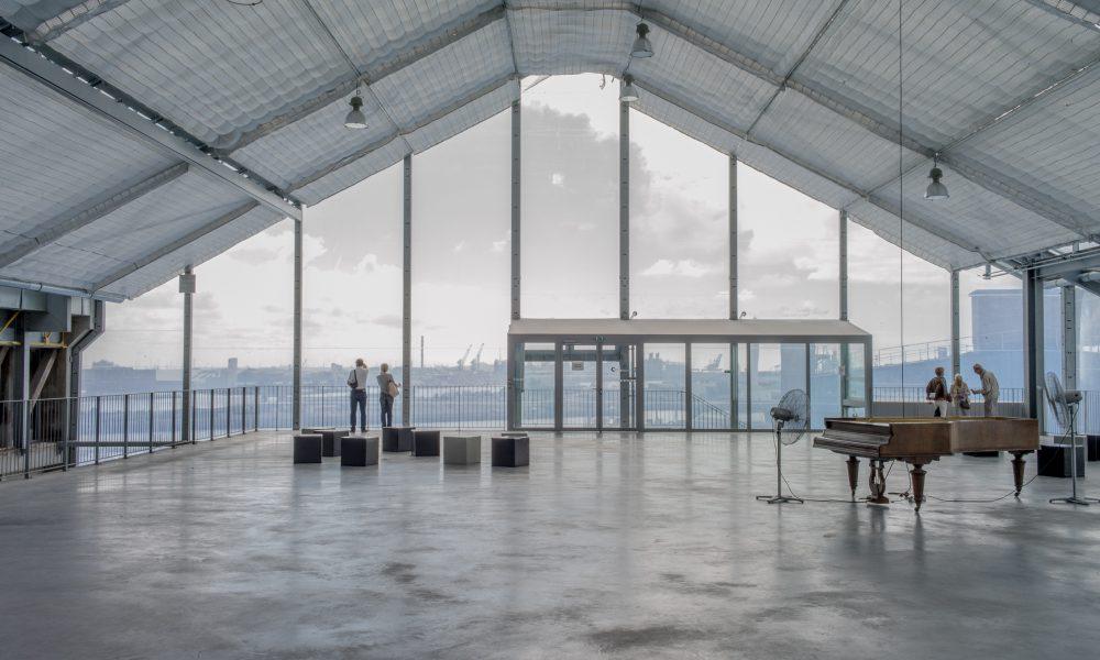 Fotografia do último piso do centro cultural FRAC onde estão pessoas a olha para a vista panorâmica  que se tem do vão aberto sobre todo o comprimento desta sala espaçosa.