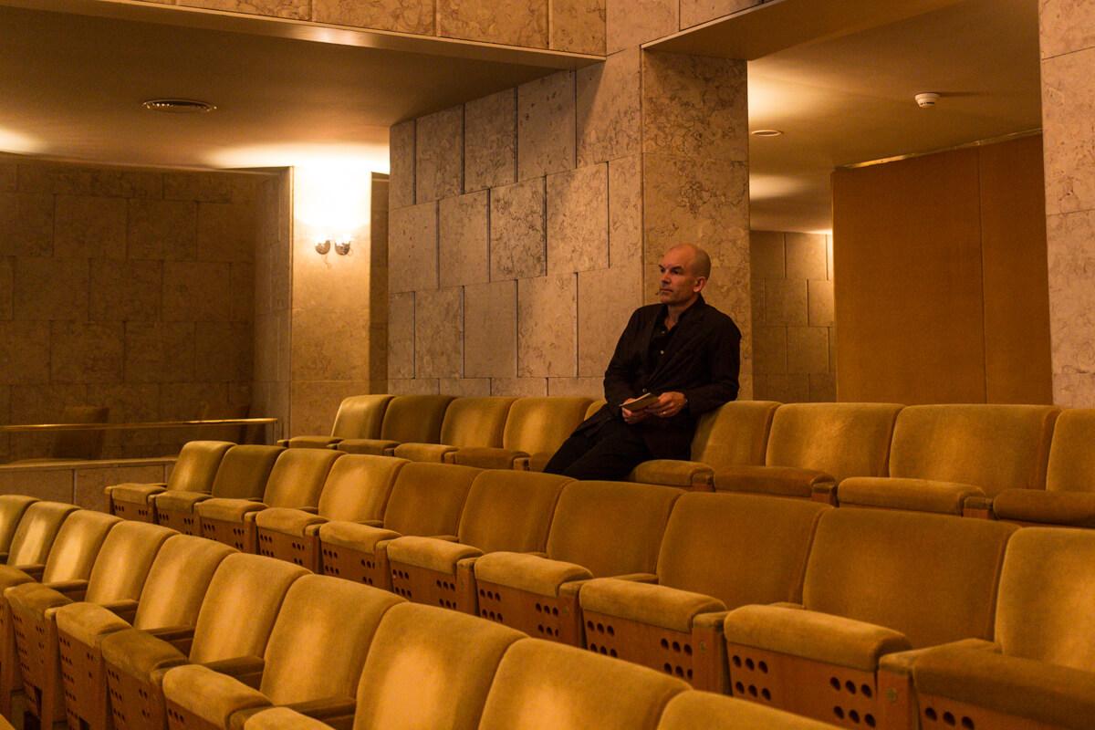 Bolle Tham à espera do início da conferência sentado numa cadeira na plateia do grande auditório do CCB